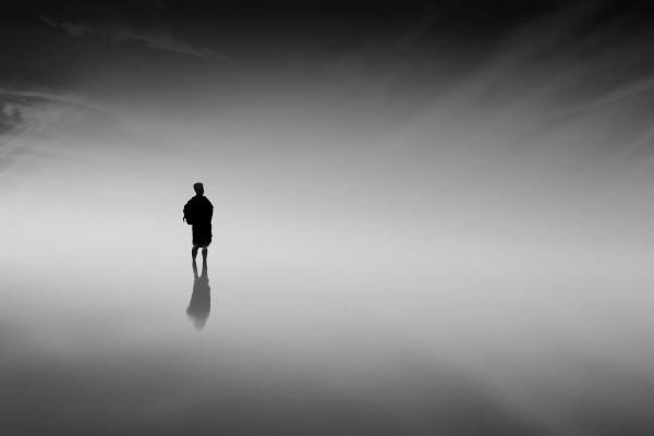 Dessin représentant un personnage au loin tout en noir, et son ombre, dans un fond de dégradés de gris et noir